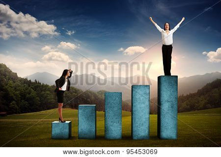 businesswoman standing at the lower step of diagram and looking up at the winner over beautiful forest landscape