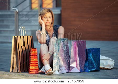 Sad young fashion woman with shopping bags sitting on a sidewalk