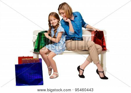 Happy  mother and daughter with shopping bags sitting at studio