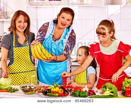 Happy family with child cooking at kitchen. Grandfather and grandmother. Four people. poster