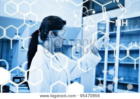 Science graphic against female chemist looking at an erlenmeyer flask