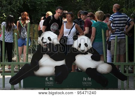 VIENNA, AUSTRIA - JUNE 7, 2015: Visitors look at the depictions of two giant pandas (Ailuropoda melanoleuca) called Long Hui and Yang Yang at Schonbrunn Zoo in Vienna, Austria.