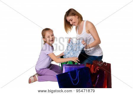 Happy a mother and daughter with shopping bags sitting at studio