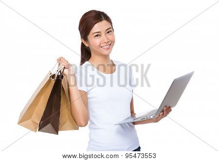 Woman use of the laptop computer and shopping bag for online shopping concept