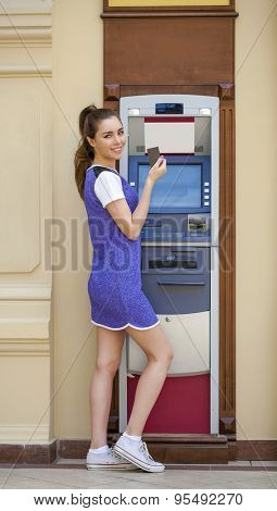 Brunette young lady using an automated teller machine. Woman withdrawing money or checking account balance