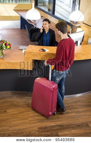 High angle view of man with luggage standing at hotel reception desk