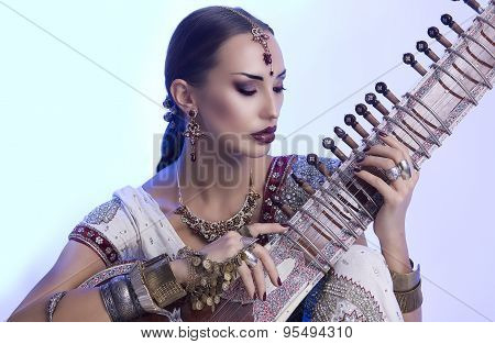 Beautiful Indian Woman In Sari With Oriental Jewelry Playing The Sitar