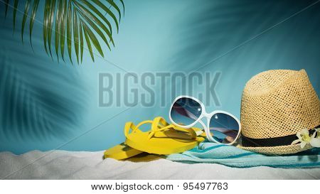 Beach accessories with sunglasses,hat,flip-flop and towel on sands