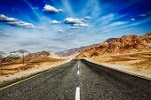 Travel forward concept background wallpaper - road in Himalayas and blue sky dramatic clouds. Ladakh, Jammu and Kashmir, India poster