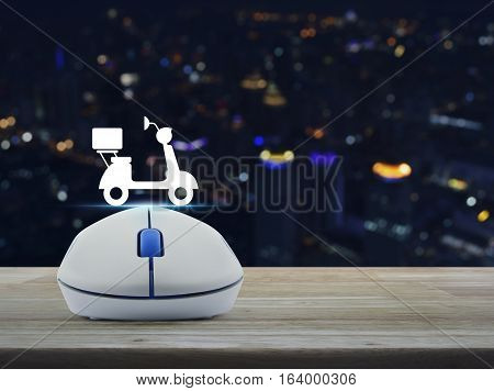 Wireless computer mouse with motor bike icon on wooden table over blur light city tower Business internet delivery service concept