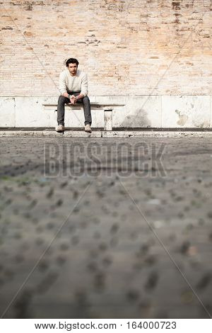 Handsome young man sitting on marble bench with bricks background. A beautiful and young boy sat on a marble bench. Behind him a large, old brick wall. Beside him, a large copyspace for custom text or graphic