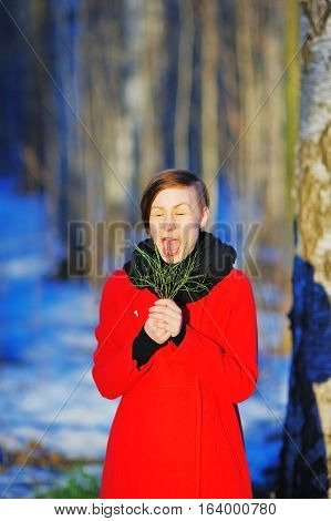 happy young woman with closed eyes and wide open mouth have fun in the snowy forest