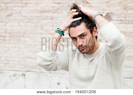 Cool young man fashion model, hairstyle. Hand in the hair. A beautiful young boy passes his hand through his hair. Intense gaze and eye-catching. Slight beard. The boy wears a white sweater and are outdoors.