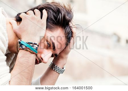 Anxiety concept. Young man with problems, despair. Close portrait of a young boy with his hands on his head and hair. Concept of tragedy, despair, problems to solve, doubt or uncertainty. Clear image with clear background.