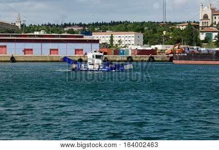 ISTANBUL TURKEY - JUNE 8 2016: Small harbour vessel being sailed around Haydarpasa Docks on the Asian side of the Bosphorus in Istanbul Turkey. Sunny afternoon in June.