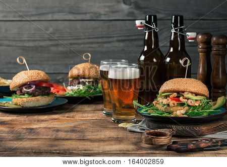 Variety of burgers with lager on the wooden table copy space