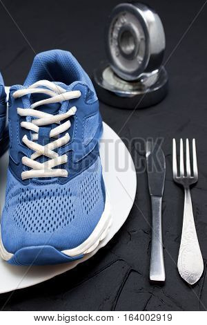 Blue sport shoes on wtite plate fork and knife on black concrete background vertical orientation. Concept healthy lifestyle sport and diet. Focus is only on the sport shoes.