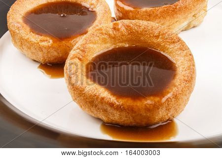 some fresh baked yorkshire pudding british food with gravey on a plate