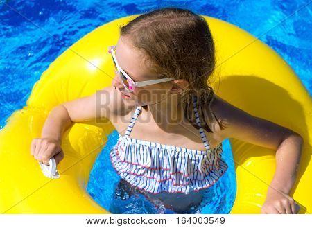 Portrait Of Little Girl With Inflatable Rubber Ring In Swimming Pool.