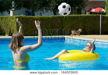 Little Girl With Her Mom Playing Ball In Swimming Pool.