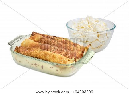 Pancakes filled with cottage cheese in the rectangular glass roasting pan and glass bowl with fresh cottage cheese on a light background