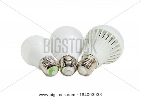 Three different domestic light emitting diode lamp with a sized E27 male screw base on a light background