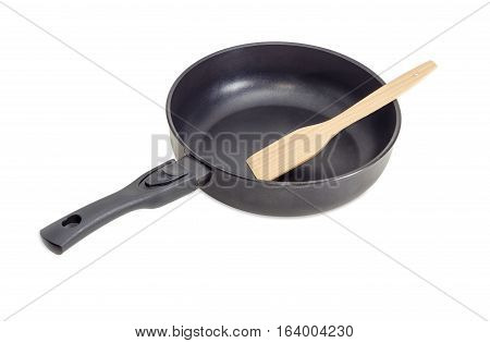 Cast frying pan made of aluminium alloy with removable handle and wooden spatula on a light background