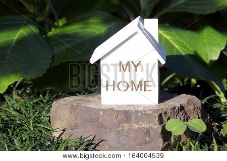 Miniature model of house on stone in the garden