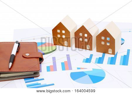 Miniature model of house on chart printed documents