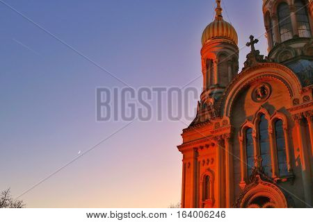 Russian greek orthodox synagogue on a stunning winter sunset.Gold dome. The moon is already visible in the background