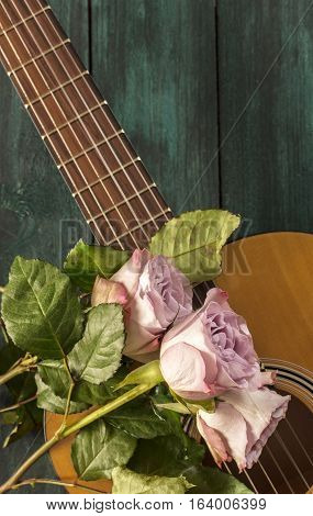 A photo of a guitar neck with tender pink roses, on a dark wooden background with copyspace
