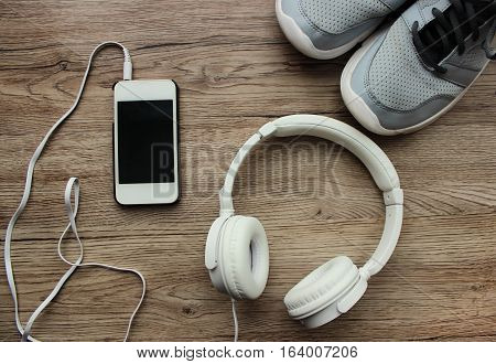 Sports kit for running: large white headphones, mobile phone, running shoes on the wooden background.