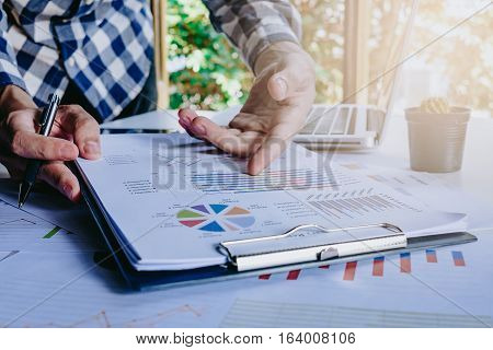 Businessman discussing the analysis charts or graphs on modern White office desk table and using laptop computer.Close up business team analysis and strategy concept with sun flare.