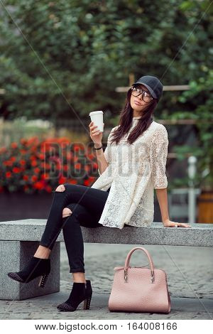 Happy asian woman resting with coffee cup in the city. Happy lovely and beautiful mixed race Asian Caucasian young girl in casual clothes with cap and handbag outdoor sitting on bench on the city street with trees and flowers. Next generation