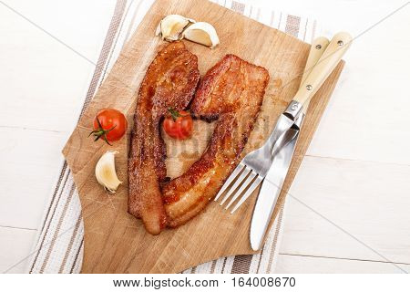 grilled spicy bacon with tomato garlic fork and knife on a wooden board