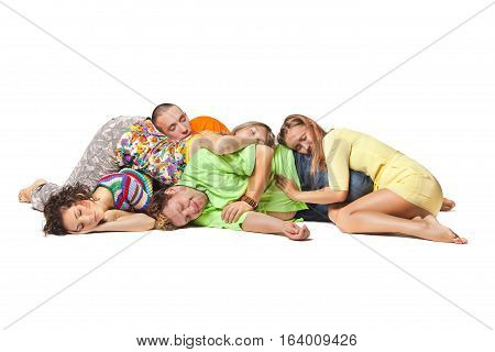 Friends lie in a heap and sleep. Group portrait of the actor lie on the floor on a white background.