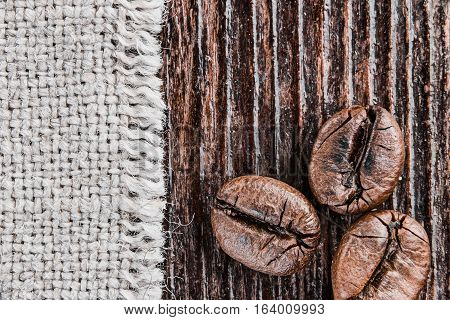 Roasted coffee beans on dark rough wood and canvas surface. Super macro view