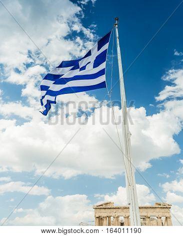 National flag of Greece on flagpole against a blue sky