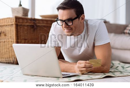 Online shopping. Pleasant delighted good looking man looking at the laptop screen and holding a credit card while making online shopping