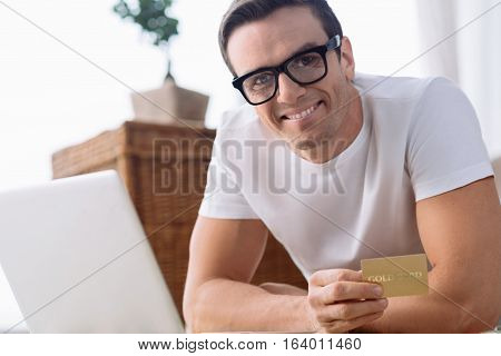 Electronic banking system. Delighted cheerful pleasant man using his electronic card and smiling while making purchases online