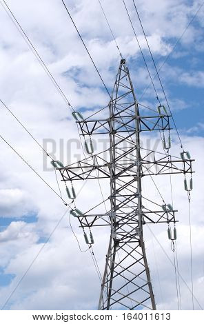 Single high-voltage power line grey metal prop with many wires over cloudy sky bottom-up view vertical oriented photo