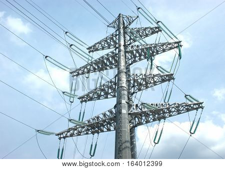 High-voltage power line grey metal prop with many wires over cloudy sky with clouds bottom-up view