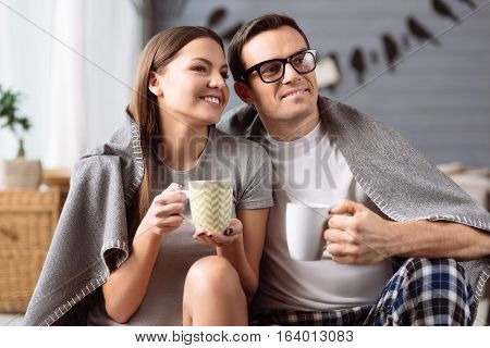 It is teatime. Pleasant happy optimistic couple sitting together and holding porcelain cups while having tea