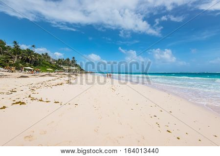 Crane Beach Barbados - December 18 2016: People relaxing on the Crane Beach Barbados Caribbean. The beach has been named as one of the ten best beaches in the world and it has the pink-tinged sands.