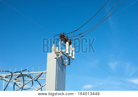 Electrical equipment unit with black wires for power supply over blue sky