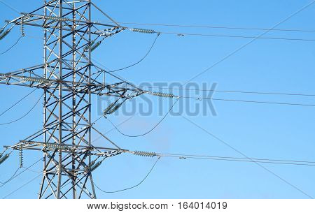 Central section of high-voltage power line grey metal support with many wires over clear cloudless blue sky