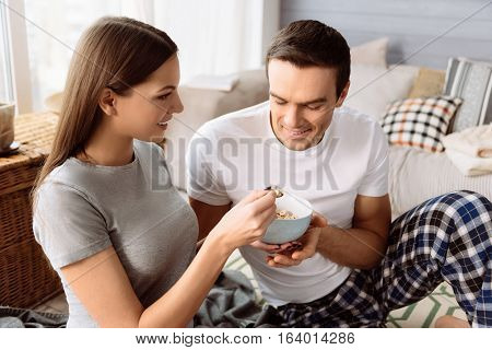 Light breakfast. Nice positive attractive woman holding a spoon and feeding her boyfriend with corn flakes while caring about him