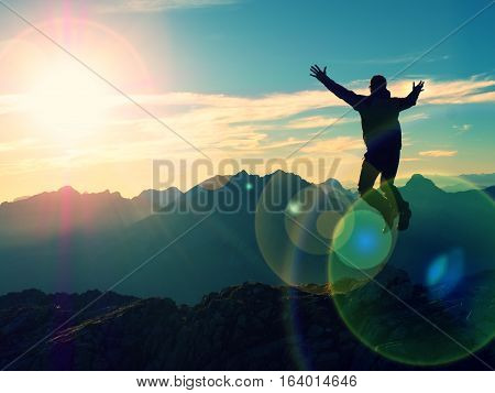 Lens Flare Effect. Bow Light Circles. Crazy Hiker Jumping At Peak Of Mountain.