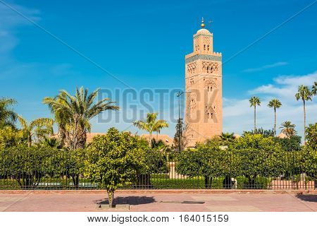 Gardens flank the Koutoubia Mosque (Kutubiyya Mosque) - the largest mosque in Marrakesh Morocco. The minaret tower which dwarfs the nearby palm trees includes a secondary tower a dome a spire of four orbs and a flag pole.
