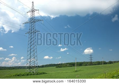 Country landscape with high-voltage power line grey metal pilons with many wires in summer day